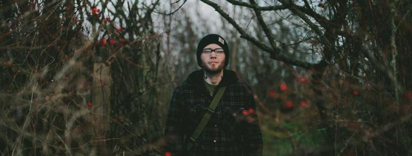 man standing in woods near beach