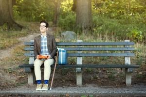 lady dressed like forrest gump sitting on bench with cane and suitcase